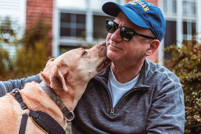 emotional support dog licking man