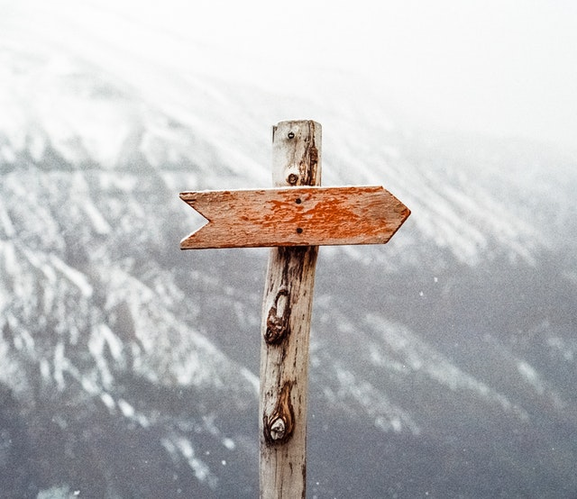 wooden arrow sign in mountains
