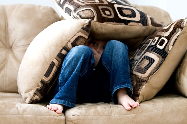 boy hiding from dog under couch pillows