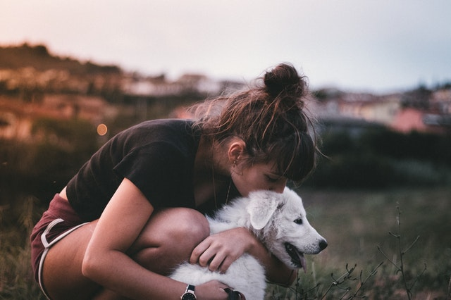 Woman hugging her dog to relieve stress and anxiety