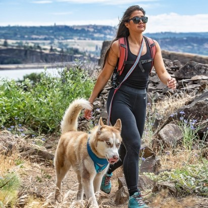 woman hiking with dog using kurgo quantum leash in over shoulder position