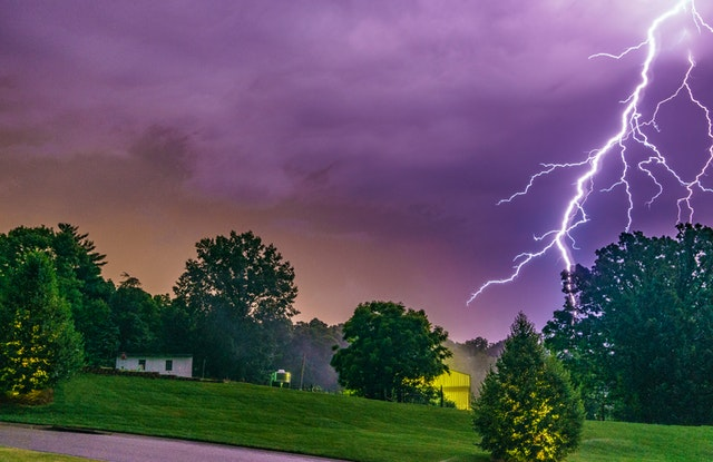 lighting striking near a house